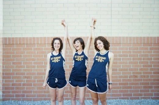 Cross Country Team Captain, Hannah, in the middle, surrounded by two teammates.